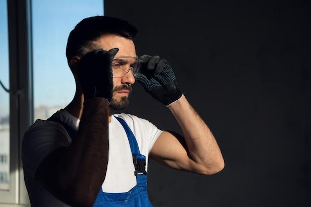 Мастер по ремонту находится в темной комнате. он надевает защитные очки