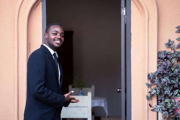 レストランとコーヒーショップのオーナーがドアを開けて、顧客を彼の店に招待しています。立って笑っているビジネスアフリカ人男性