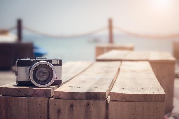 Ретро-камера на деревянном столе с размытым морским фоном.