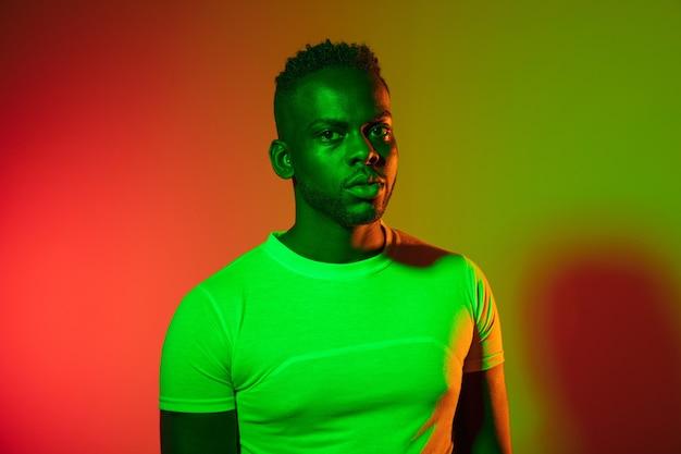 スタジオで若い幸せな真面目なアフリカ人のレトロな波またはシンセ波の肖像画。黒の背景にポーズをとるカラフルな明るいネオンライトのハイファッション男性モデル。アートデザインコンセプト