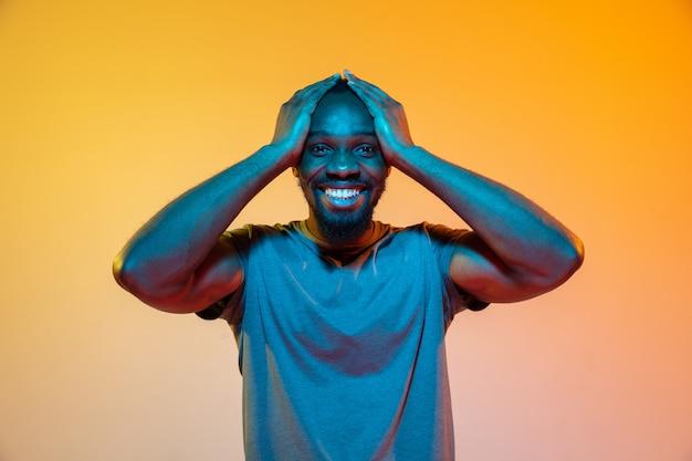 Ретро волна волны или synth развевает портрет молодого счастливого серьезного африканского человека на студии.