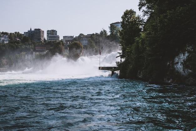 Рейнский водопад - самый большой водопад в европе в шаффхаузене, швейцария. летний пейзаж, солнечная погода, голубое небо и солнечный день