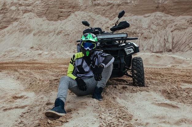 ライダーは砂の上に座ってatvに寄りかかった