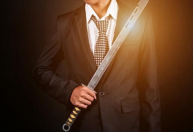 Правая рука бизнесмена, держащего меч на темном фоне.