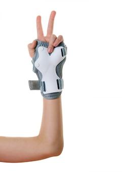 白い背景で隔離の保護に身を包んだ子供の右手。衝撃保護用のアクセサリー。