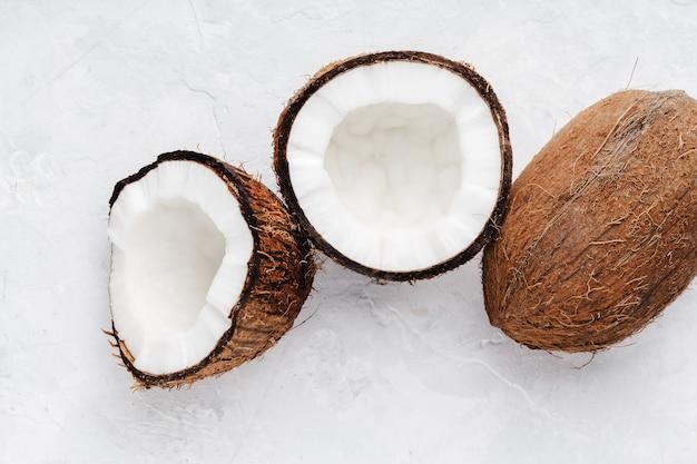 익은 코코넛은 밝은 배경에 반으로 쪼개지고 전체 코코넛이 닫히고 위쪽