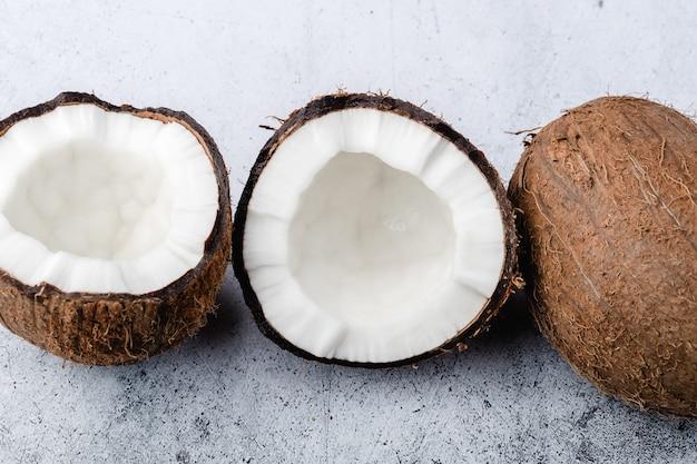 익은 코코넛은 밝은 회색 배경에 전체 코코넛이 반으로 나뉘며 닫혀 있고 위쪽