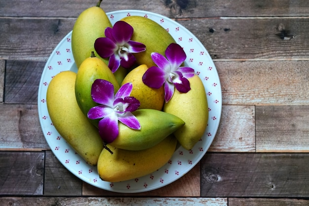 Спелые манго барракуда с украшать цветок орхидеи дендробиум на тарелке на деревянном фоне