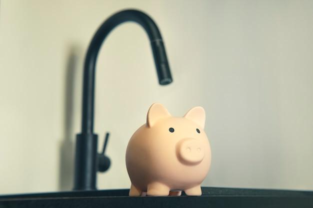 住宅と共同サービスの価格の上昇。シンクの金属製の蛇口と貯金箱。節水コンセプト