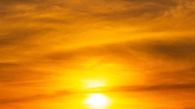 Восходящее солнце ярко светит в оранжевом небе.