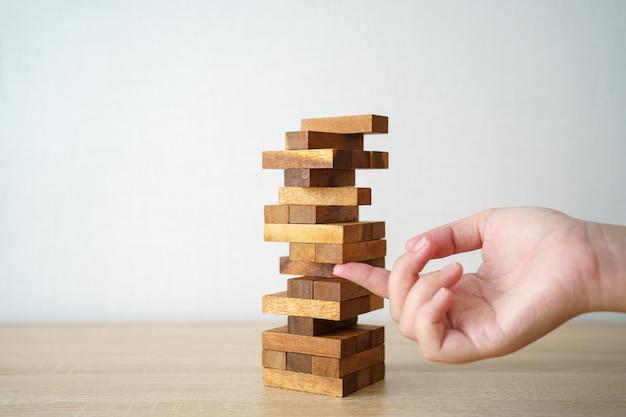 나무 테이블에서 블록 나무 게임을하는 엔지니어의 손
