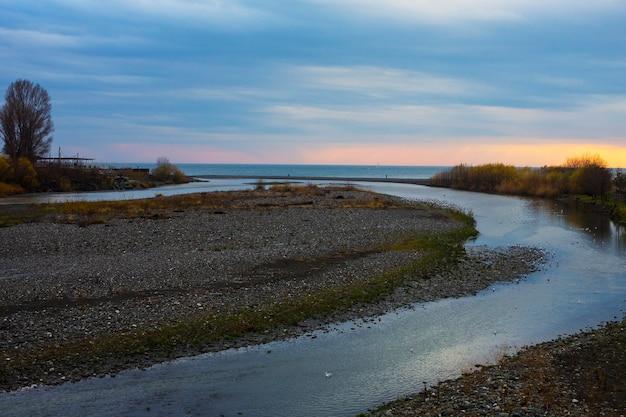 川は海に流れ込みます。ロシア、ソチのアドレル地区の黒海に流れ込むムジムタ川の河床の眺め。日没時に海に流れる山川