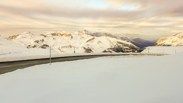 Дорога среди снега на горе на закате