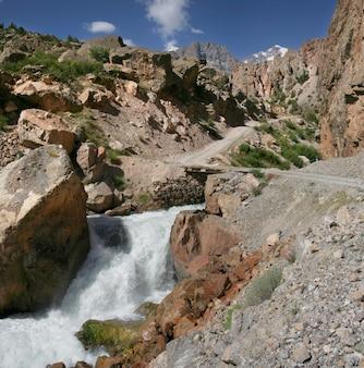 タジキスタンのパミール高原の山々の道。嵐の川に架かる橋。