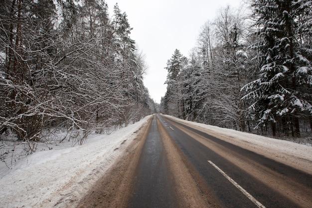 겨울철 도로, 청소 후 도로는 녹은 눈으로 뒤덮여 있으며, 그 길을 지나는 수많은 자동차