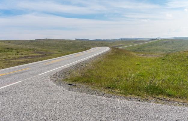 Дорога тянется вдаль на фоне зеленых лугов.