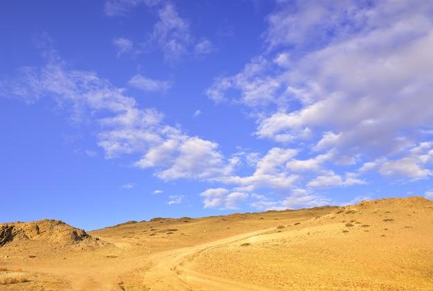 푸른 하늘로 가는 길 흐린 하늘 아래 봄에 쿠라이 대초원의 바위 비탈