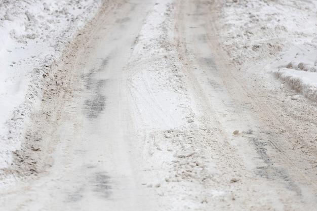 車道は雪に覆われ、車のタイヤの跡が残っています。高品質の写真