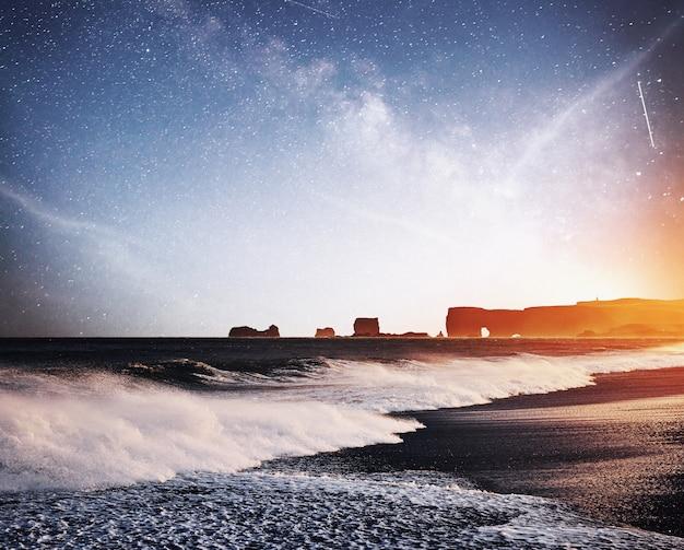 Рок тролль пальцы. рейнисдрангарские скалы. черный песчаный пляж. фантастическое звездное небо и млечный путь