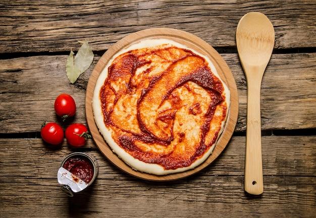롤아웃 피자 반죽에 토마토 페이스트와 토마토.