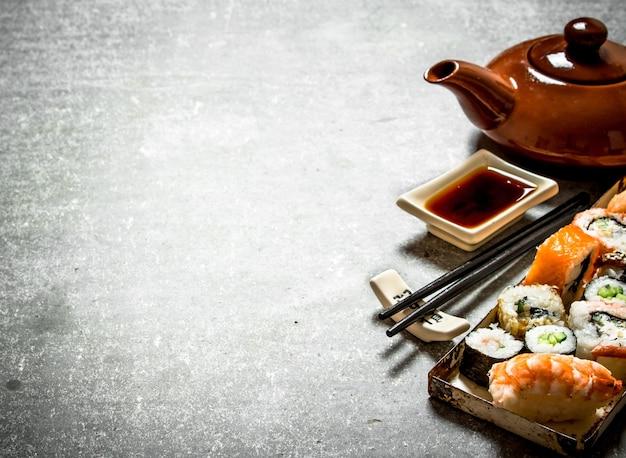Роллы и суши, травяной чай и соевый соус. на каменном столе.