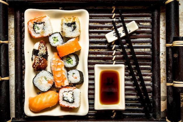 トレイに醤油をかけたロールと寿司プレート。