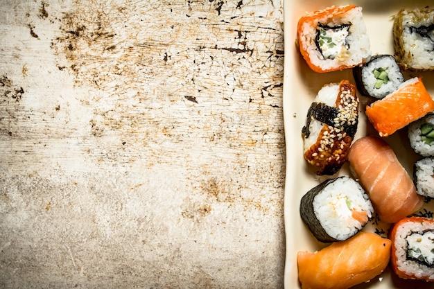 Роллы и суши, морепродукты на тарелке. на деревенском фоне.