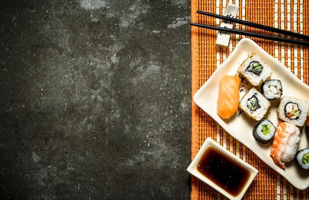 Роллы и суши с соевым соусом на бамбуковой подставке.