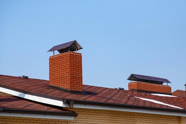 Крыша коттеджа со скатами оклада дымохода на фоне голубого неба коричневая крыша из битумной черепицы.