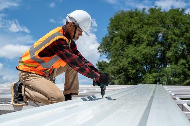 Техники-кровельщики работают и устанавливают новую конструкцию крыши на крыше дома, металлическую крышу, крепят гофрированные листы.