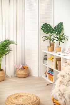 部屋は明るい色で、緑の植物があります。休息のための居心地の良いコーナー