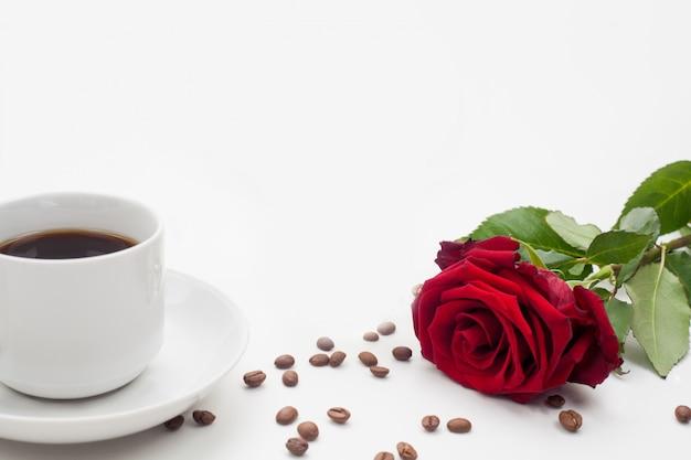 Роза и кофейная чашка украшены кофейными зернами на белой стене внизу текстового пространства.