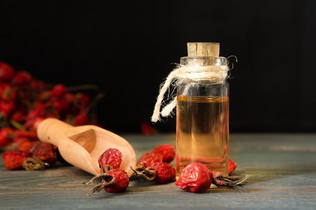 Масло шиповника на деревянных досках на темном фоне. флакон с эфирным маслом шиповника перевязан шнурком.