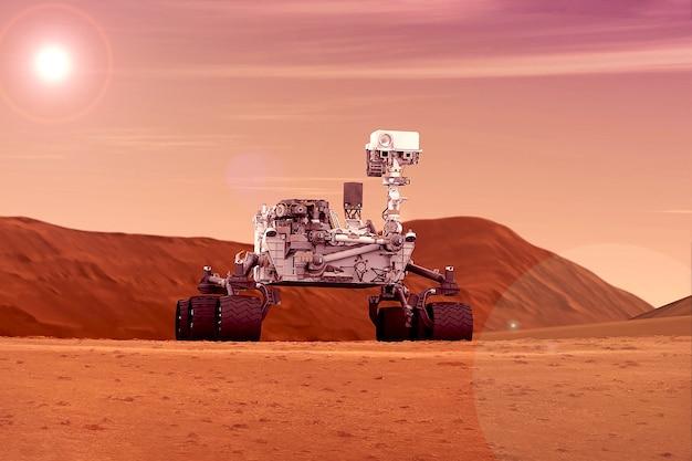 ローバーは惑星の平原を探索します。太陽が地平線上にある。この画像の要素はnasaによって提供されました。あらゆる目的のために。
