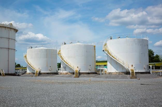 Ряд небольших белых резервуаров для автозаправочных станций и запчастей для нефтеперерабатывающих заводов.