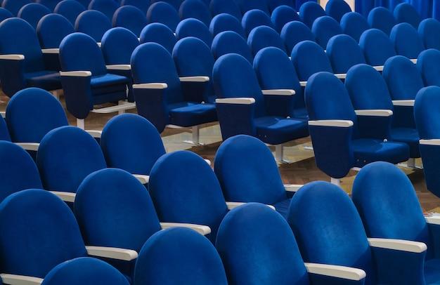 영화관이나 회의장에 빈 파란색 좌석이 줄지어 있습니다.