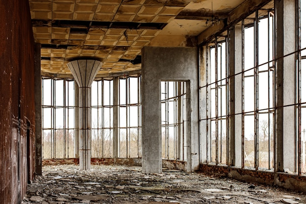 넓은 창문이 있는 오래된 건물의 폐허가 된 홀. 바닥에 깨진 유리입니다.