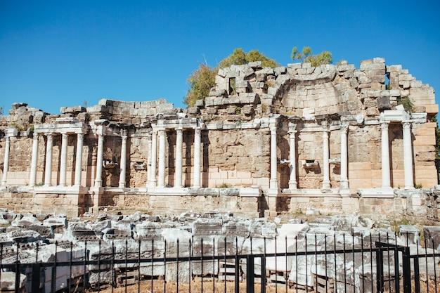 Руины разрушенного театра в городе сиде турция. греческие остатки архитектуры в малой азии. путешествие и достопримечательности курортных городов.
