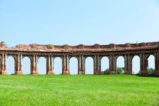 Руины изображают древнюю крепость 16 века, расположенную в селе ружаны гродненской области, беларусь, разрушенную арку на фоне голубого неба.