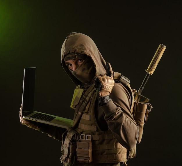 ラップトップで暗い背景に武器を持った軍服を着た妨害兵