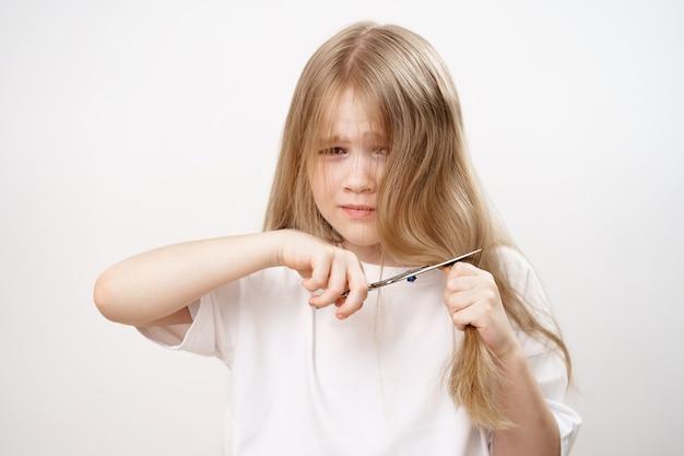 Грустная маленькая девочка стрижет ножницами длинные волосы и боится на белом фоне. модная стрижка для малышки. парикмахер. детские шалости. стрижка волос