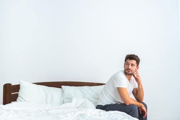 白い背景の上のベッドに座っている悲しい男