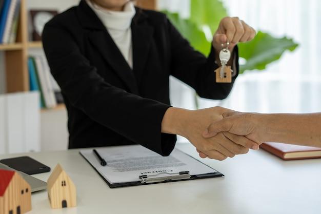 영업 담당자가 악수를하고 새 주택 소유자에게 열쇠를 전달합니다.