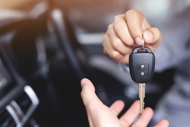 Продавец передает ключи от новой машины покупателю в автосалоне.