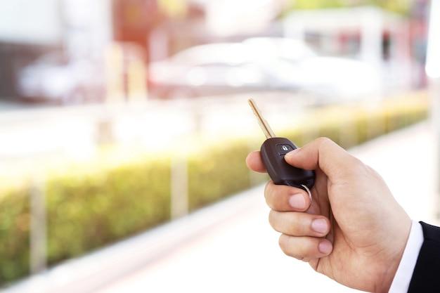 Продавец открывает и закрывает дверь машины ключом. для безопасности