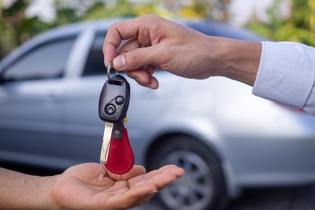 판매원은 여성 고객의 손에 자동차 키를 보내고 있습니다. 매매계약을 성공적으로 체결한 후