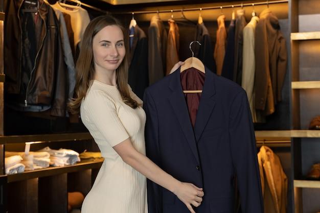 店員さんが笑顔でコスチュームショップで洋服を見せてカメラに向かって話します