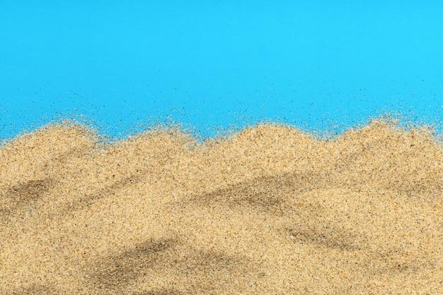 Песок, изолированные на синей поверхности
