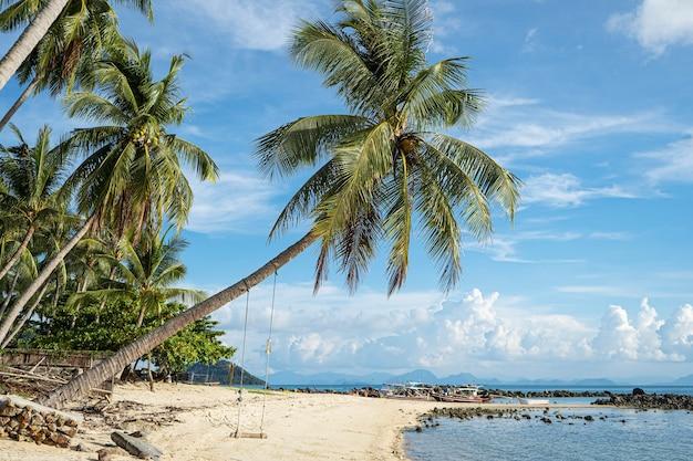 푸른 바다 파도의 모래 해변과 그네가있는 야자수