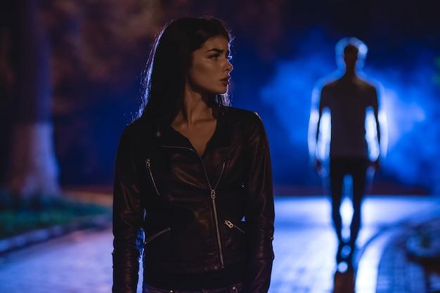 Испуганная женщина стоит на темной улице на фоне мужчины. ночное время